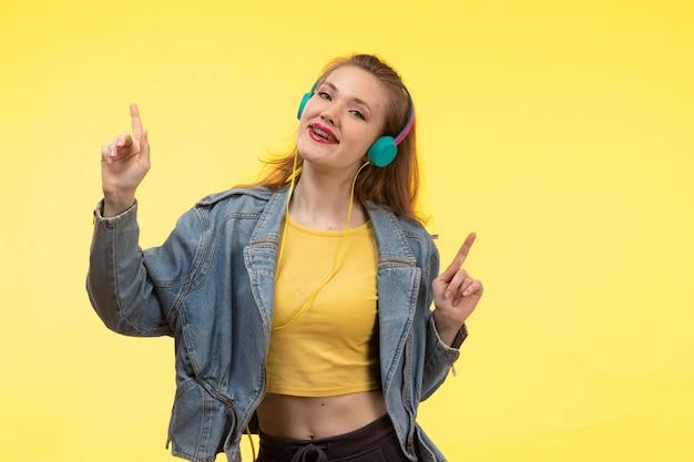 Widok z przodu młoda nowoczesna kobieta w żółtych koszulowych czarnych spodniach i płaszczu jean z kolorowymi słuchawkami słuchającymi muzyki