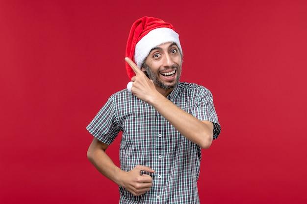 Widok Z Przodu Młoda Osoba Z Uśmiechniętym Wyrazem Twarzy Na Czerwonej ścianie Wakacje Nowy Rok Czerwony Darmowe Zdjęcia
