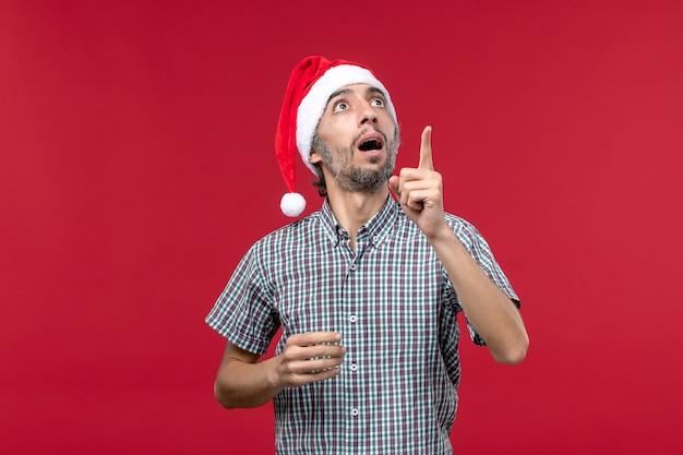 Widok Z Przodu Młoda Osoba Z Zaskoczonym Wyrazem Na Czerwonej ścianie Czerwony Mężczyzna Wakacje Nowego Roku Darmowe Zdjęcia