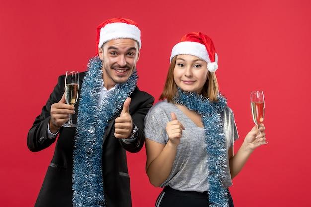 Widok z przodu młoda para świętuje nowy rok na czerwonej podłodze, kocha świątecznego drinka