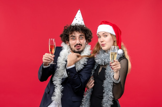 Widok z przodu młoda para świętuje nowy rok na czerwonej podłodze wakacje boże narodzenie przyjęcie miłosne