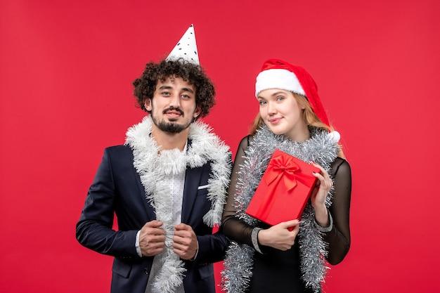 Widok z przodu młoda para świętuje nowy rok na czerwonej ścianie boże narodzenie miłość wakacje