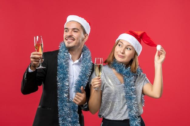 Widok z przodu młoda para świętuje nowy rok na czerwonej ścianie kocha świątecznego drinka