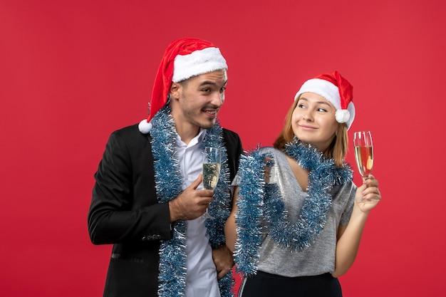 Widok z przodu młoda para świętuje nowy rok na czerwonej ścianie miłość przyjęcie bożonarodzeniowe