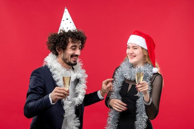 Widok z przodu młoda para świętuje nowy rok na czerwonej ścianie party holiday boże narodzenie miłość
