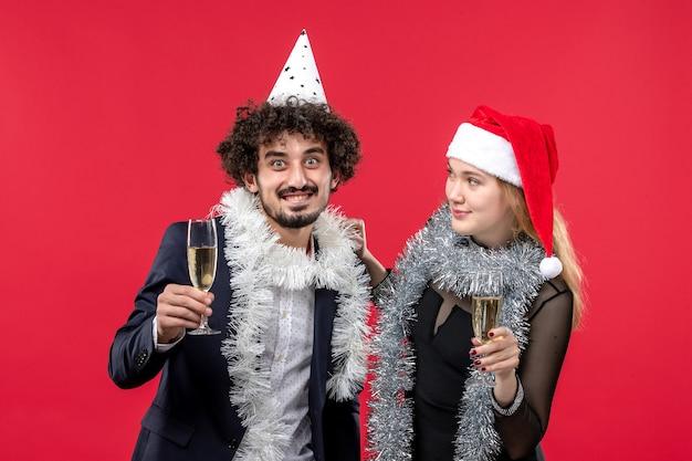 Widok z przodu młoda para świętuje nowy rok na czerwonej ścianie wakacje miłość przyjęcie świąteczne