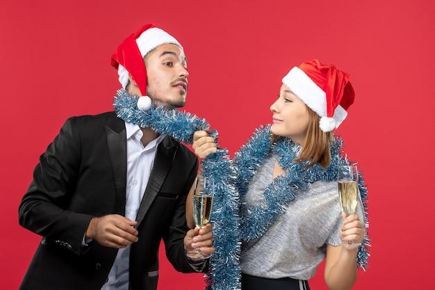Widok z przodu młoda para świętuje nowy rok na czerwonym biurku, kocha świątecznego drinka