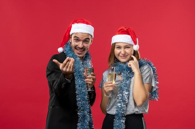 Widok z przodu młoda para świętuje nowy rok na czerwonym biurku, kocha święta bożego narodzenia