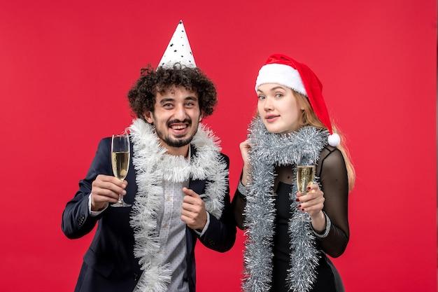 Widok z przodu młoda para świętuje nowy rok na czerwonym biurku miłość przyjęcie bożonarodzeniowe