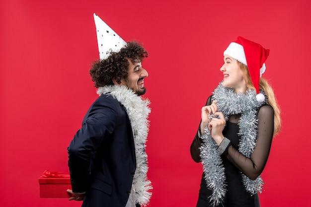 Widok z przodu młoda para wymiany prezentów świątecznych na czerwonej ścianie emocja miłość boże narodzenie