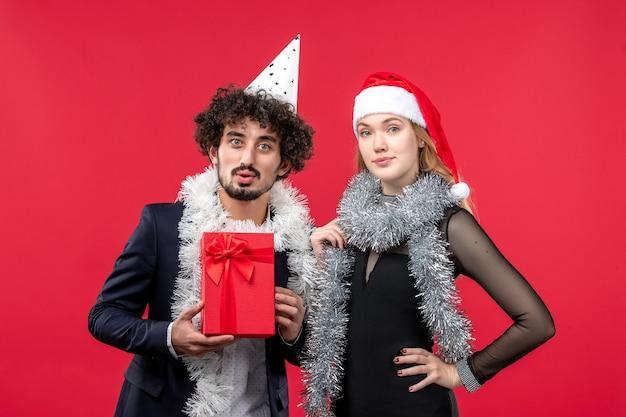 Widok z przodu młoda para z teraźniejszością świętuje na czerwonej ścianie przyjęcie bożonarodzeniowe