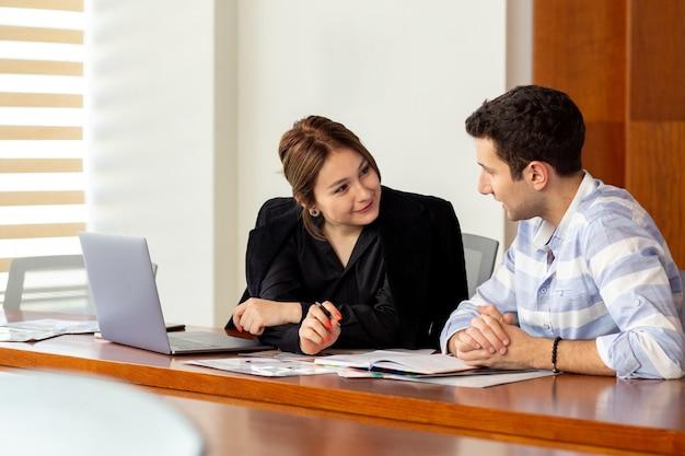 Widok z przodu młoda piękna bizneswoman w czarnej koszuli czarnej kurtce wraz z młodym mężczyzną omawiającym kwestie pracy w jej biurowym budynku pracy