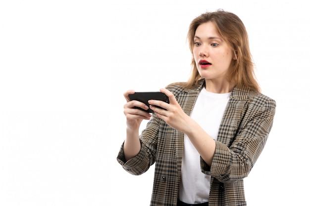Widok z przodu młoda piękna dama w białej koszulce, czarnych dżinsach i płaszczu za pomocą smartfona zaskoczona na białym tle