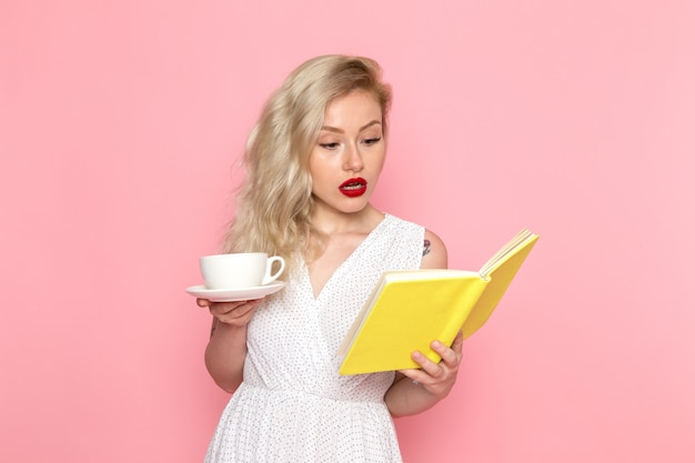 Widok z przodu młoda piękna dama w białej sukni picia herbaty czytając zeszyt