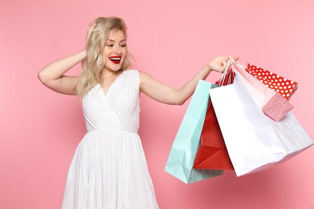 Widok z przodu młoda piękna dama w białej sukni trzymając pakiety zakupów z uśmiechem na twarzy