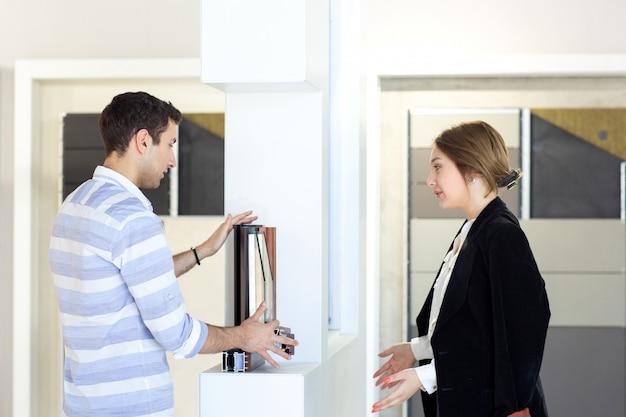 Widok z przodu młoda piękna dama w ciemnych czarnych spodniach w białej koszuli wraz z młodym mężczyzną omawiającym pracę podczas wykonywania pracy w ciągu dnia