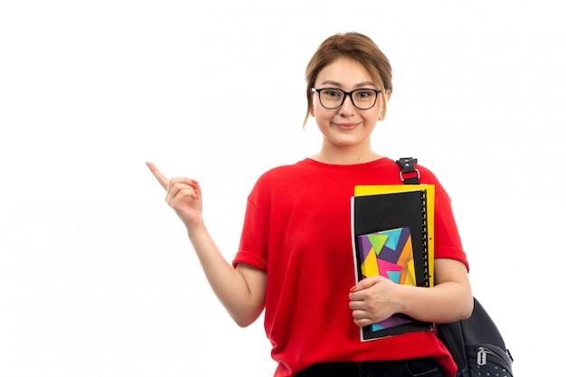 Widok z przodu młoda piękna dama w czerwonej koszulce czarne dżinsy trzymając różne zeszyty i pliki uśmiecha się z torbą na białym