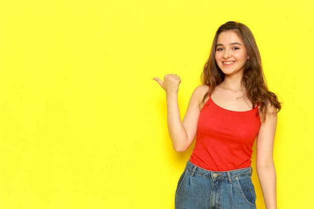 Widok z przodu młoda piękna dama w czerwonej koszuli i niebieskich dżinsach pozuje z zachwyconym podekscytowanym wyrazem