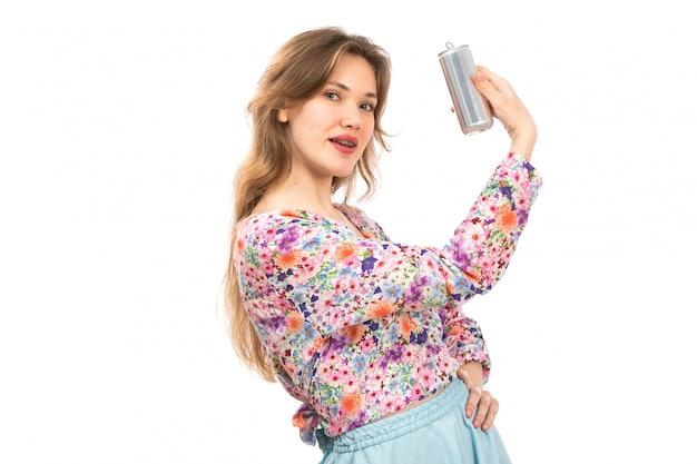 Widok z przodu młoda piękna dama w koszuli w kolorowe kwiatki i niebieskiej spódnicy, trzymając srebrną puszkę na białym