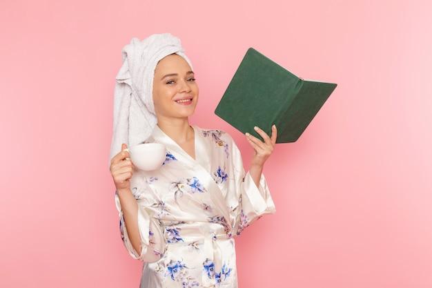 Widok z przodu młoda piękna dama w szlafroku trzymając książkę i czyta picie kawy