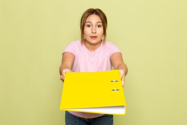 Widok z przodu młoda piękna dziewczyna w niebieskich dżinsach różowy t-shirt pozowanie i rozdaje żółty plik na zielono