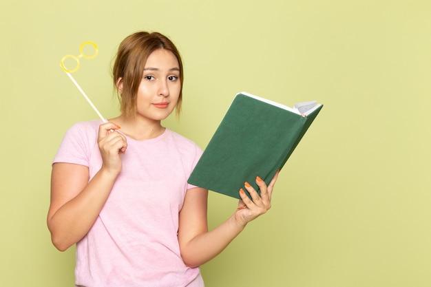 Widok z przodu młoda piękna dziewczyna w niebieskich dżinsach różowy t-shirt pozowanie z zabawkowymi okularami przeciwsłonecznymi, czytając książkę na zielono