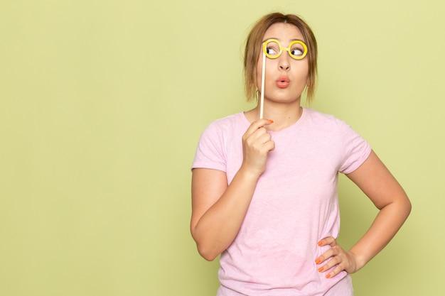 Widok z przodu młoda piękna dziewczyna w niebieskich dżinsach różowy t-shirt pozuje z zabawkowymi okularami przeciwsłonecznymi na zielono