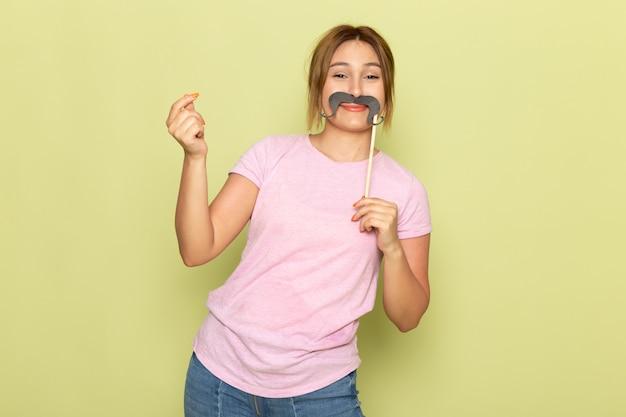 Widok z przodu młoda piękna dziewczyna w niebieskich dżinsach różowy t-shirt z fałszywymi wąsami na zielono