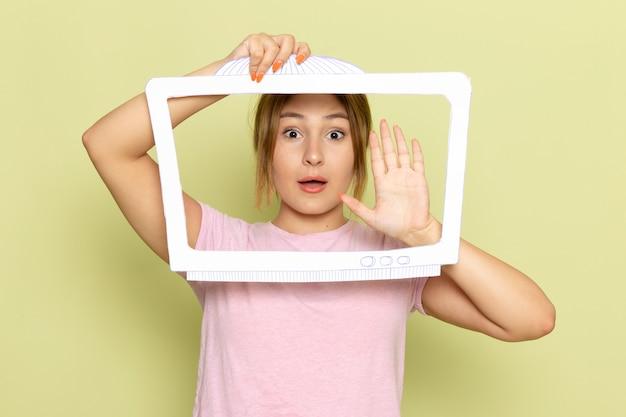 Widok z przodu młoda piękna dziewczyna w różowej koszulce z białym papierem w kształcie telewizora na zielono