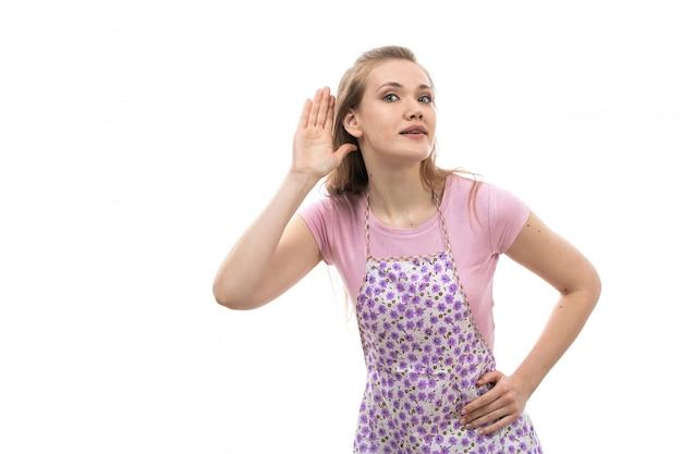 Widok z przodu młoda piękna gospodyni w różowej koszuli kolorowe peleryny próbuje usłyszeć pozowanie