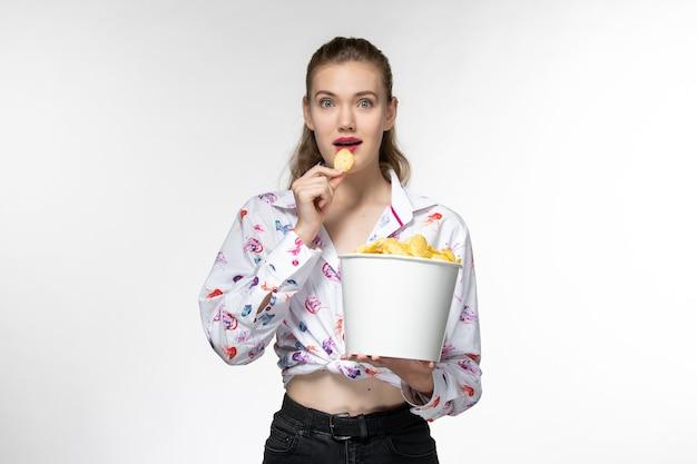 Widok z przodu młoda piękna kobieta trzyma kipsy ziemniaczane jedzenie na białej powierzchni