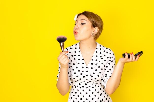 Widok z przodu młoda piękna kobieta w czarno-białej sukience w kropki robi makijaż na żółtym tle odzież moda tusz do rzęs pędzel