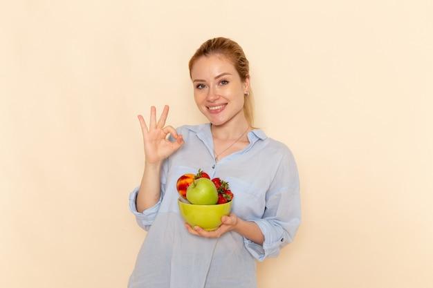 Widok z przodu młoda piękna kobieta w koszuli trzymając talerz z owocami uśmiechając się na ścianie kremu stanowią dojrzałe kobiety modelki owoców