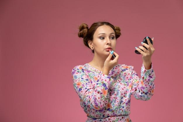 Widok z przodu młoda piękna kobieta w koszuli zaprojektowanej w kwiatki i niebieskie dżinsy robi makijaż na różowym tle
