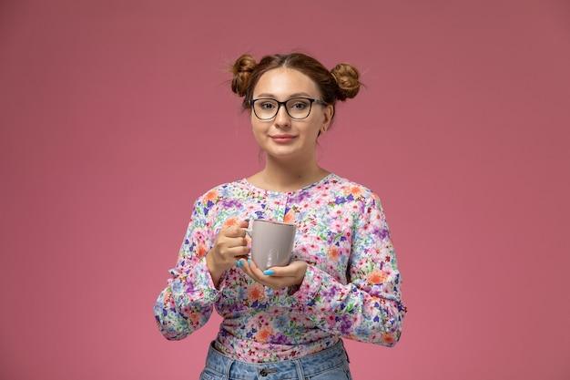 Widok z przodu młoda piękna kobieta w kwiatowej koszuli i niebieskich dżinsach trzyma filiżankę herbaty z uśmiechem na różowym tle