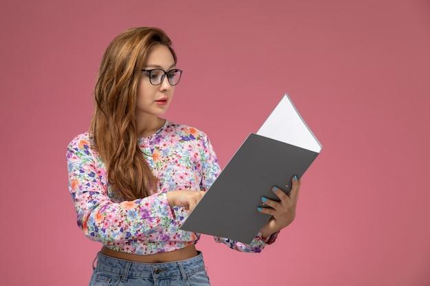 Widok z przodu młoda piękna kobieta w kwiatowej koszuli i niebieskich dżinsach, trzymając czytanie szarego dokumentu na różowym tle