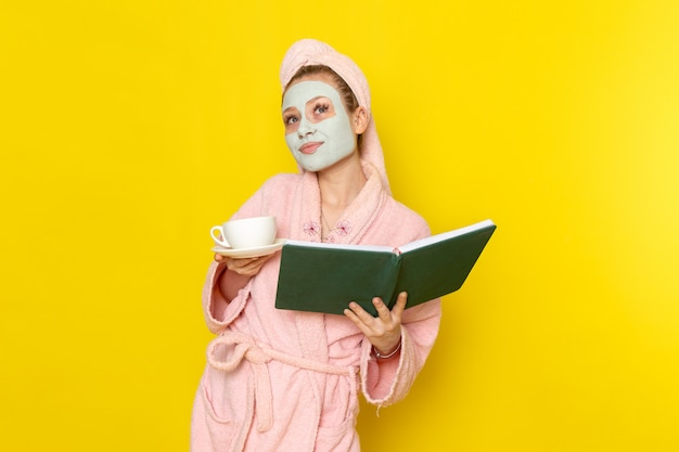 Widok z przodu młoda piękna kobieta w różowym szlafroku, trzymając zieloną książkę i filiżankę herbaty