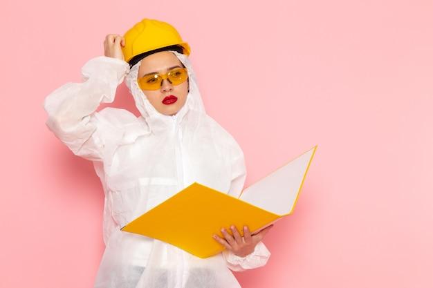 Widok z przodu młoda piękna kobieta w specjalnym białym garniturze na sobie kask ochronny, trzymając żółty plik na różowej przestrzeni specjalnej kobiety garnitur