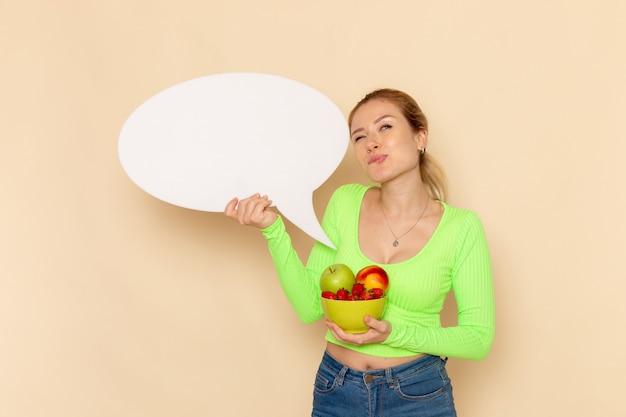 Widok z przodu młoda piękna kobieta w zielonej koszuli trzymając talerz pełen owoców z białym napisem na ścianie kremu model owoców kobieta jedzenie witamina kolor