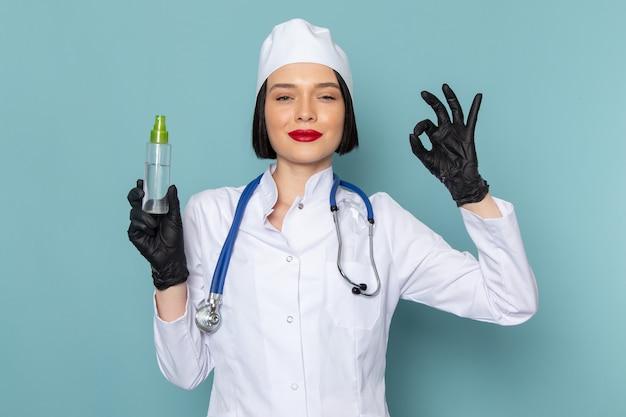 Widok z przodu młoda pielęgniarka w białym garniturze i niebieskim stetoskopie trzymając spray na niebieskim biurku lekarz szpitala