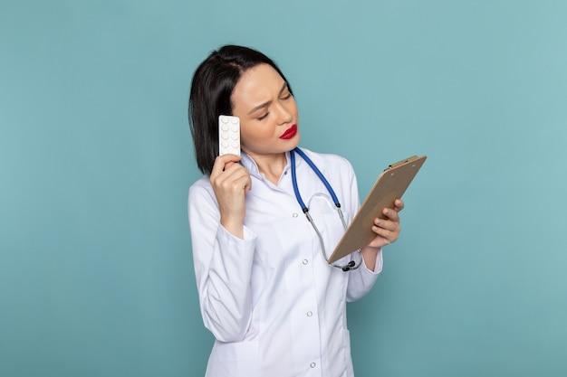 Widok z przodu młoda pielęgniarka w białym garniturze medycznym i niebieskim stetoskopie gospodarstwa notatnika
