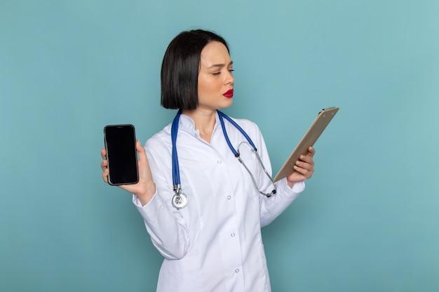 Widok z przodu młoda pielęgniarka w białym garniturze medycznym i niebieskim stetoskopie, trzymając notatnik i telefon