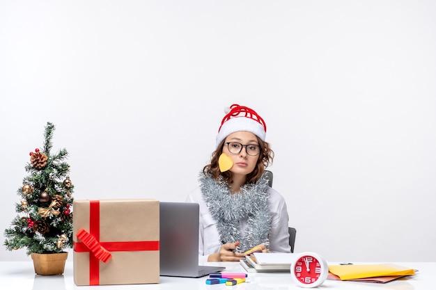 Widok z przodu młoda pracownica siedzi przed swoim miejscem pisania notatek na białym tle