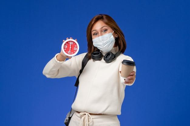 Widok z przodu młoda studentka w białej jersey na sobie maskę i plecak trzyma kawę i zegar na niebieskiej ścianie