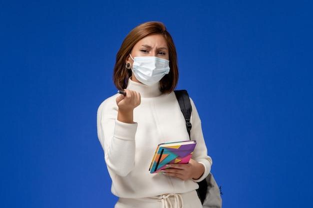 Widok z przodu młoda studentka w białej jersey nosząc maskę z torbą i zeszytem z piórem na niebieskim biurku lekcja college university school