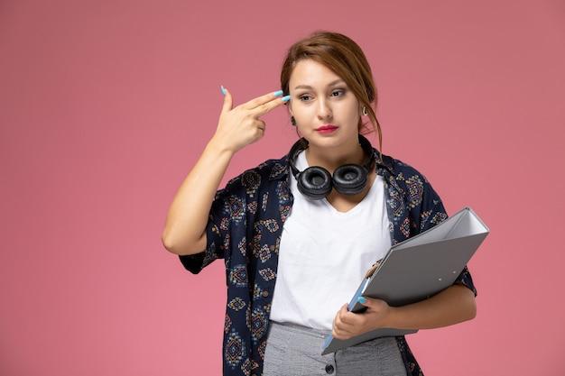 Widok z przodu młoda studentka w białej koszulce i szarych spodniach pozuje i myśli na różowym tle lekcje dla studentów uczelni