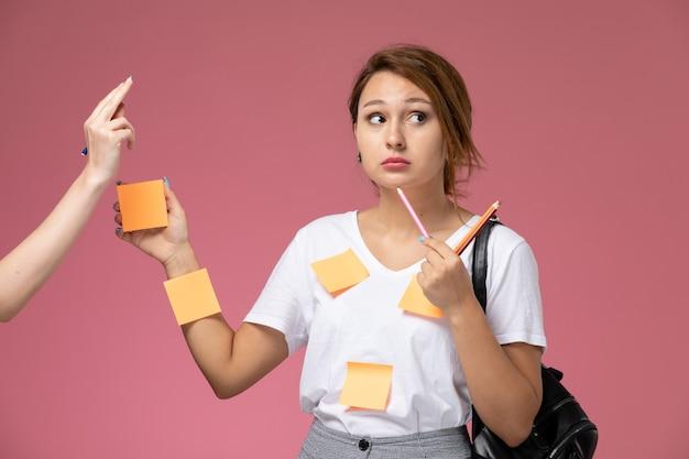Widok z przodu młoda studentka w białej koszulce i szarych spodniach pozuje z ołówkami i papierami na różowym tle lekcje dla studentów uczelni