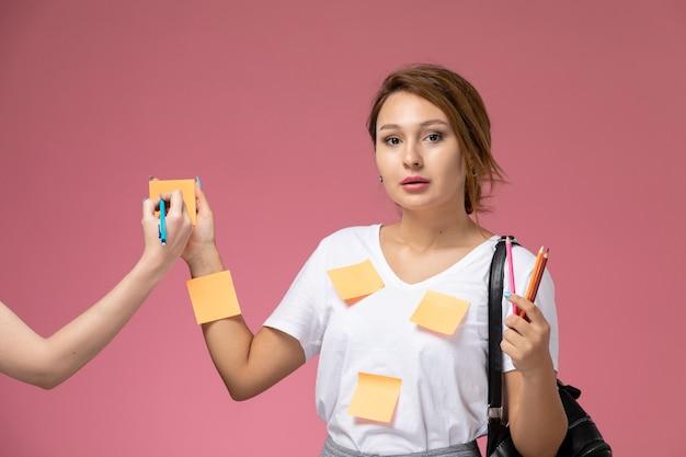 Widok z przodu młoda studentka w białej koszulce i szarych spodniach pozuje z ołówkami na różowym tle lekcje dla studentów uczelni