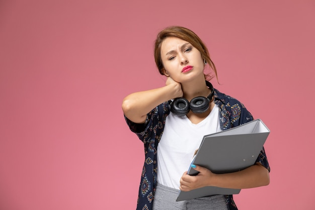 Widok z przodu młoda studentka w białej koszulce i szarych spodniach uśmiecha się z plikiem słuchawki na różowym tle lekcje dla studentów uczelni