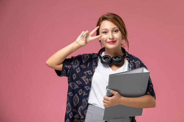 Widok z przodu młoda studentka w białej koszulce i szarych spodniach uśmiecha się ze słuchawkami na różowym tle lekcje dla studentów uczelni